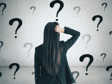 Foto de Back view of young businesswoman on concrete wall background with question marks. Confusion and choice concept - Imagen libre de derechos