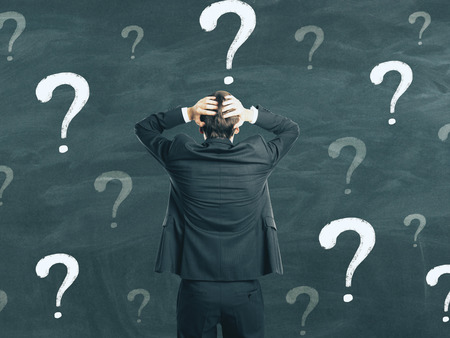 Photo pour Back view of young businessman on chalkboard wall background with question marks. Confusion and think concept - image libre de droit