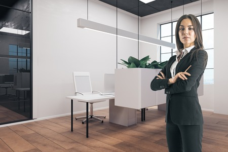 Young businesswoman with folded arms standing in modern office interior.
