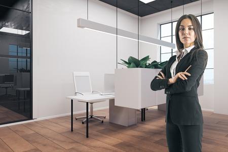 Foto de Young businesswoman with folded arms standing in modern office interior. - Imagen libre de derechos