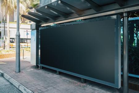 Foto de Side view of empty black horizontal billboard at bus stop. Commercial concept. Mock up - Imagen libre de derechos
