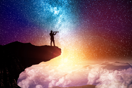 Side view of young backlit businessman on cliff looking into the distance through binoculars glass on creative starry sky space background. Vision and fantasy concept