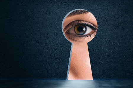 Photo pour Abstract keyhole opening with eye on concrete wall background. Access and vision concept - image libre de droit