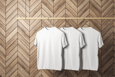 Foto de Empty three white tshirts on hanger. Wooden tile wall background. Design, store and style concept. Mock up, 3D Rendering - Imagen libre de derechos