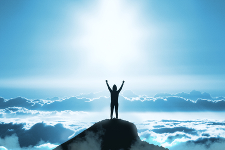 Foto de Back view of young backlit person standing on mountain top on blue sky with clouds background. Success and leadership concept - Imagen libre de derechos