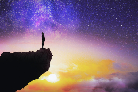 Foto de Tiny man silhouette on cliff standing on beautiful starry sky background with sunset. Purpose and way concept - Imagen libre de derechos