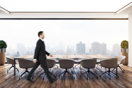 Photo pour Side view of attractive young european businessman walking in modern meeting room with city view. Executive and boss concept. - image libre de droit
