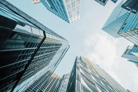 Foto de Bottom view of skyscrapers on bright blue sky background. Urban and lifestyle concept - Imagen libre de derechos
