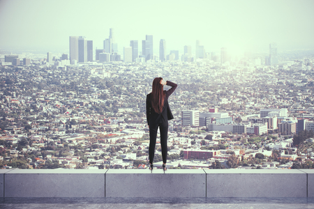 Photo for Back view of young woman on rooftop looking at city with daylight. Research and vision concept - Royalty Free Image