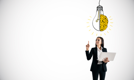 Photo pour Attractive young businesswoman with laptop pointing at creative light bulb brain sketch on white background. Idea and brainstorm concept - image libre de droit