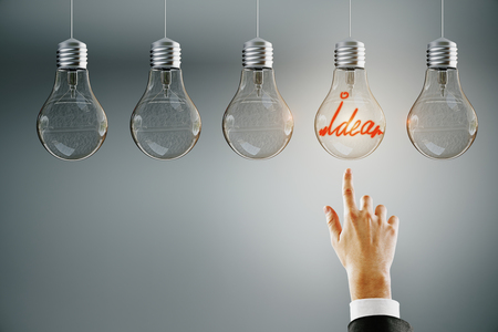 Photo pour Hand pointing at row of illuminated light bulbs on subtle background. Leadership, idea and choice concept - image libre de droit