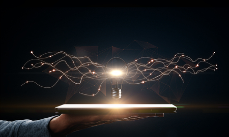 Photo for Hand holding tablet with creative glowing lamp on dark background. Idea and science concept. - Royalty Free Image
