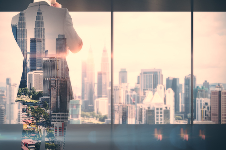 Back view of thoughtful young businessman standing in modern business interior with Kuala Lumpur city view. Success and research concept. Double exposure