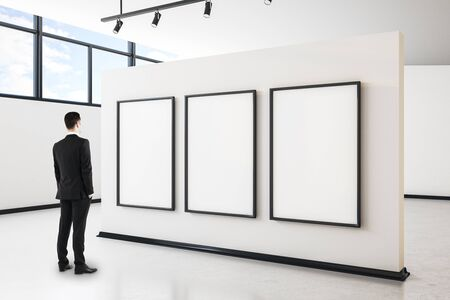 Photo pour Businessman in modern gallery interior with city view, empty poster and daylight. Mock up, - image libre de droit