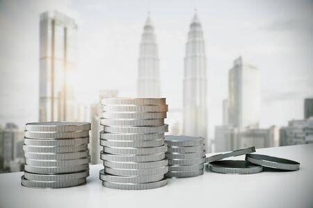 Photo pour Creative silver coin piles on blurry Kuala Lumpur city background. Money and income concept. 3D Rendering - image libre de droit