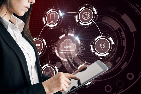 Photo pour Attractive businesswoman using tablet with creative glowing cloud computing interface on dark background. Backup and storage concept. Double exposure - image libre de droit