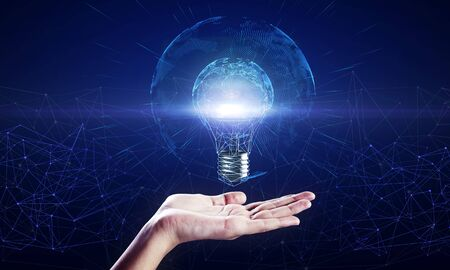Photo for Hand holding glowing polygonal light bulb with globe on dark blue background. Worldwide innovation and interface concept - Royalty Free Image