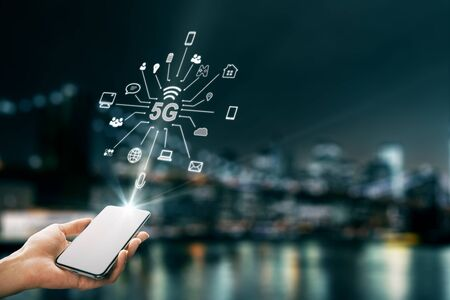 Photo for Hand using smartphone with abstract 5G interface with computing icons on blurry night city background. Internet speed and ai concept. Double exposure - Royalty Free Image