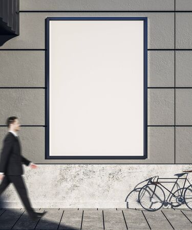 Photo pour Businessman walking past empty concrete exterior wall with bicycle on street, empty poster and sunlight. Mock  up, - image libre de droit