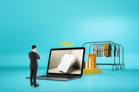 Photo for Creative online shopping concept with businessman looking at huge laptop and racks with clothes on blue background. - Royalty Free Image