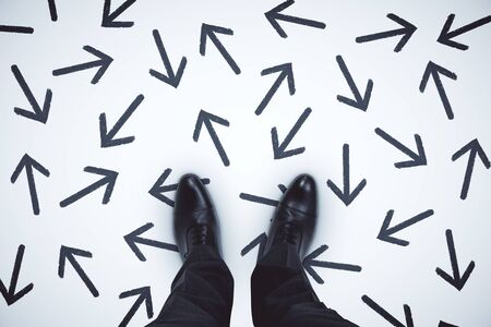Photo pour Top view of businessman feet with arrows on grey background. - image libre de droit
