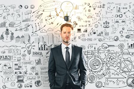 Photo for Thoughtful young businessman with glowing light bulb and business sketch on concrete wall background. Idea and education concept - Royalty Free Image