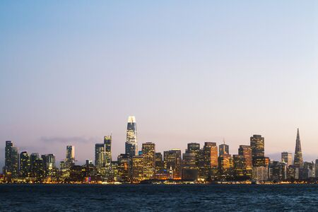 Photo for Modern waterfront San Francisco city skyline background with illuminated buildings at dawn. Urban architecture concept - Royalty Free Image