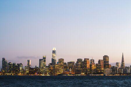 Photo pour Modern waterfront San Francisco city skyline background with illuminated buildings at dawn. Urban architecture concept - image libre de droit