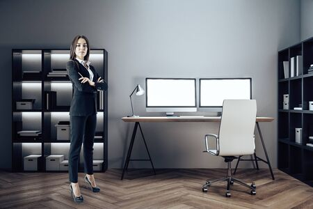 Businesswoman standing in designer interior with two empty computer screen and lamp on table