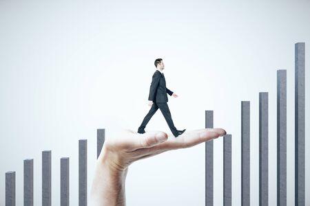 Foto de Hand helps a businessman climb on a business graph on white background.  Success and startup concept. - Imagen libre de derechos