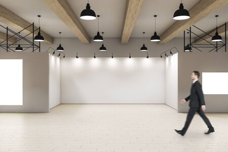 Photo pour Businessman walking in modern gallery interior. Art and design concept. - image libre de droit