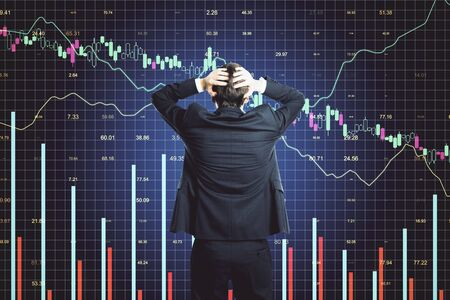 Photo pour Scared businessman looking on glowing stock analytics on virtual screen. Global business and information technology concept - image libre de droit