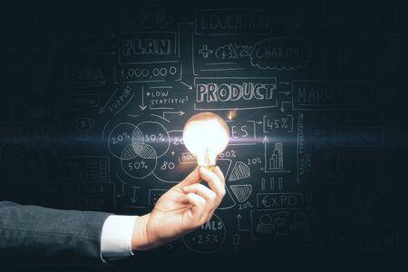 Foto de Businessman hand holding light bulb and drawing global business marketing plan. Trade and business analysis concept. - Imagen libre de derechos