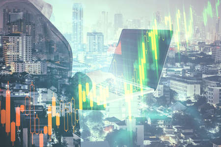 Photo pour Businesswoman using laptop on blurry city background with forex chart. Trade and technology concept. Double exposure - image libre de droit