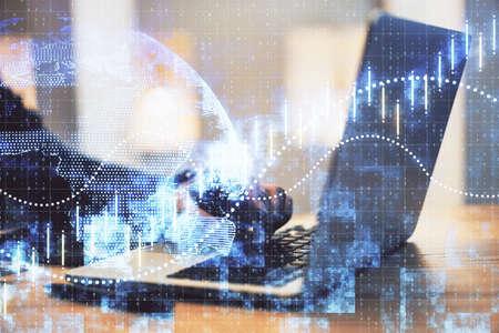 Photo pour Hand using laptop computer with business charts. Finance and trade concept. Multiexposure - image libre de droit