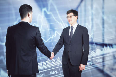 Foto de Two businessmen in suits shaking hands on the background of financial chart in office, deal and partnership concept - Imagen libre de derechos