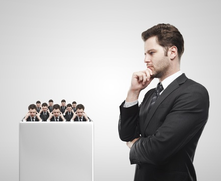 Young  businessman look at the group of businessmen on a white pedestal. Thinking men representing a social network. Conceptual image of a open minded men.On a gray background