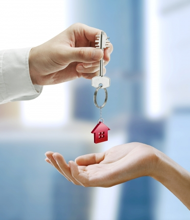 Foto de Man is handing a house key to a woman.Key with a keychain in the shape of the house. - Imagen libre de derechos