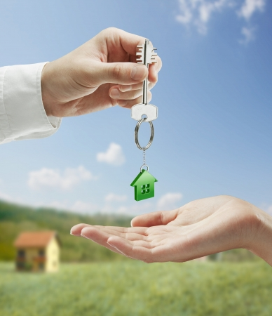 Man is handing a house key to a woman.Key with a keychain in the shape of the house. On background of nature