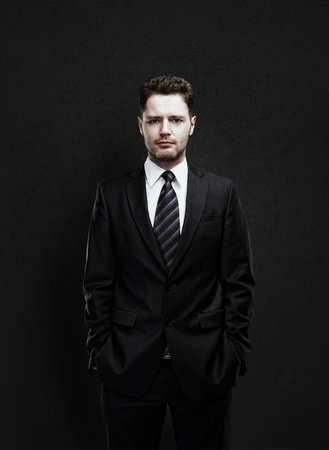 Portrait of a young businessman standing with his hands in the pockets  Young handsome man  looking confident  On a black  background
