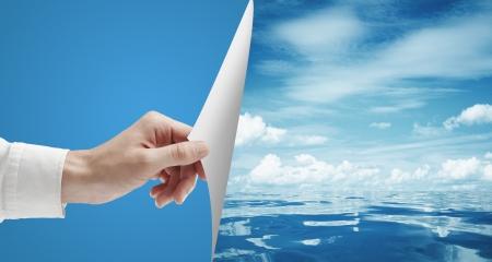 Foto de hand turn page to still sea surface - Imagen libre de derechos