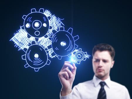 Photo pour man drawing gears on a blue background - image libre de droit