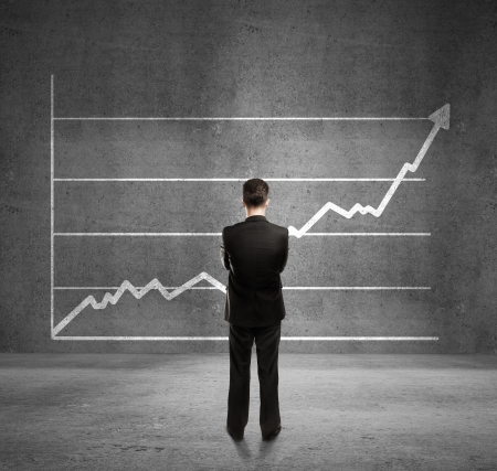 businessman looks at growth chartの写真素材