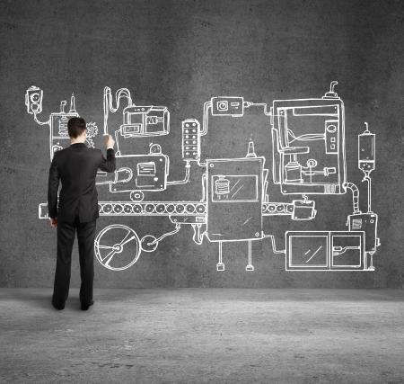 businessman drawing plan mechanism on wall