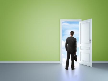 man in green room with door in sky
