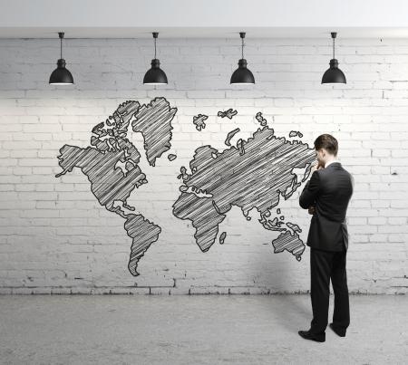 man looking at  world map on brick wall