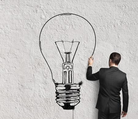 Foto de businessman drawing lamp on wall - Imagen libre de derechos