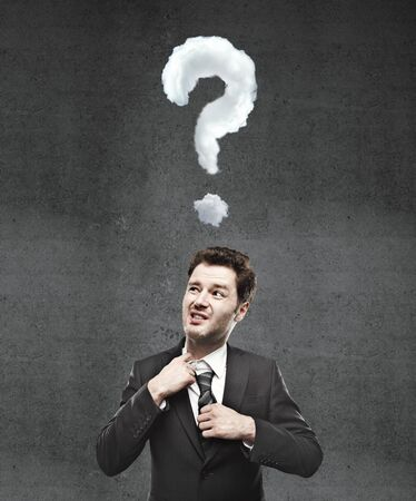 businessman thinking with question mark and concrete wall