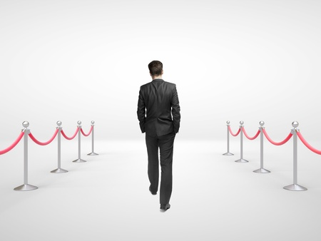 businessman walking and stanchions barrier in white room