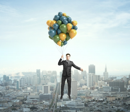 businessman flying with air baloons over the city